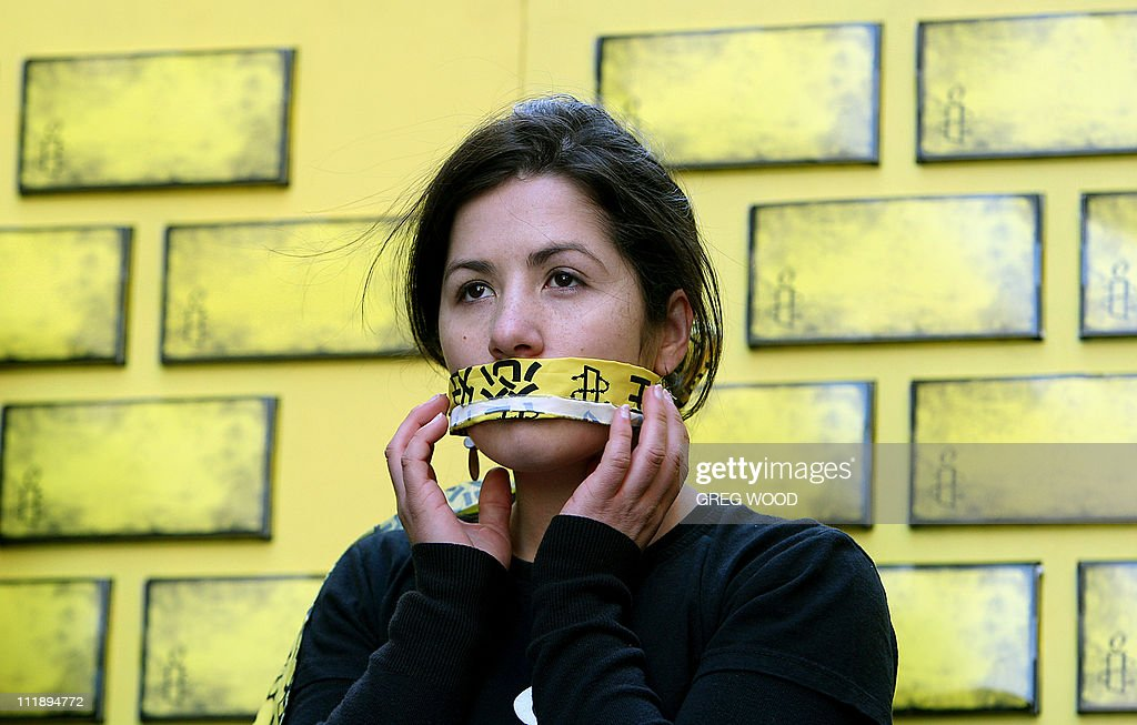An Amnesty International member covers her mouth during an event in Sydney on July 30, 2008 as part of a campaign to end internet censorship in China. With the Beijing Olympic Games fast approaching, Amnesty International who are concerned about the involvement of internet companies in censorship in China, were encouraging Sydney-siders to tear down a 20-metre yellow wall stacked with cardboard bricks and which represents the 'Great Firewall of China'. AFP PHOTO / Greg WOOD