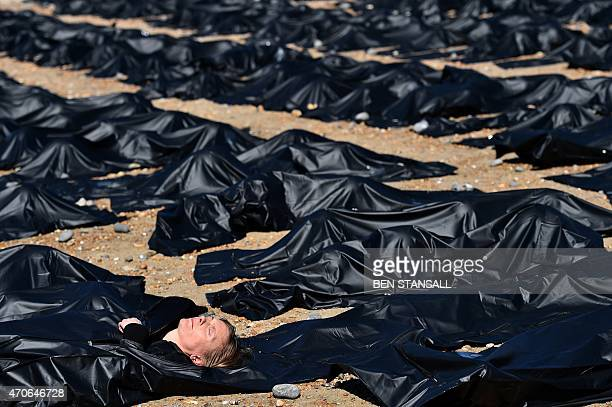 An Amnesty International supporter is pictured in a 'body bag' on Brighton beach in southern England on April 22 during a photocall by Amnesty...