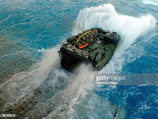 An amphibious assault vehicle exits the well deck of USS Fort McHenry.