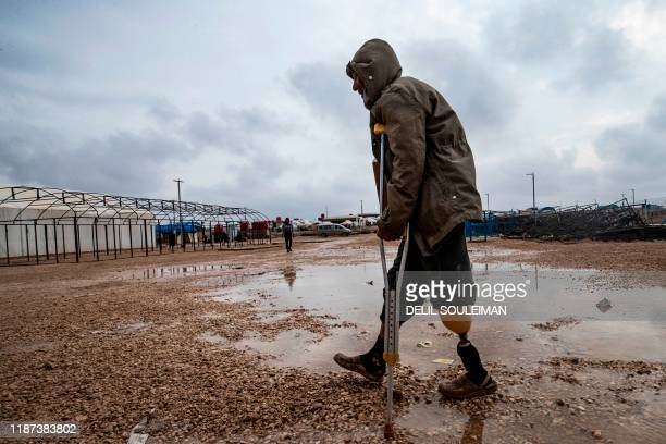 TOPSHOT An amputee man walks on crutches at the Kurdishrun alHol camp for the displaced where families of Islamic State foreign fighters are held in...