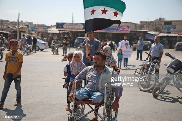 An amputee propels his wheelchair as a girl behind him raises the flag of the Syrian opposition during a demonstration against the Syrian regime and...