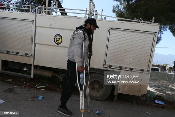 TOPSHOT An amputee walks in the village of Qalaat alMadiq some 45 kilometres northwest of the central city of Hama on March 26 after Syrian civilians...