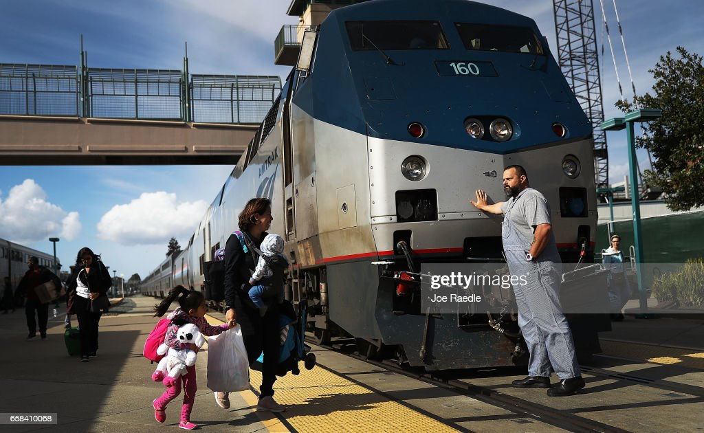 An Amtrak engineer leans on the locomotive as passengers disembark from Amtrak's California Zephyr at the end of its daily 2,438-mile trip to Emeryville/San Francisco from Chicago that took roughly 52 hours on March 25, 2017 in Emeryville, California. President Trump has proposed a national budget that would terminate federal support for Amtrak's long distance train services, which would affect the California Zephyr and other long distance rail lines run by Amtrak.
