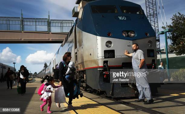 An Amtrak engineer leans on the locomotive as passengers disembark from Amtrak's California Zephyr at the end of its daily 2438mile trip to...