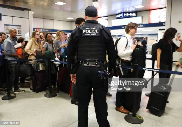 An Amtrak police officer stands guard as people wait for trains at Pennsylvania Station one of Manhattan's main transportation hubs on the eve of the...