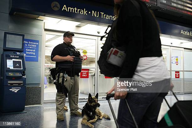 An Amtrak police officer stands guard with a K9 as Transportation Secretary Ray LaHood speaks to the media regarding national highspeed rail service...