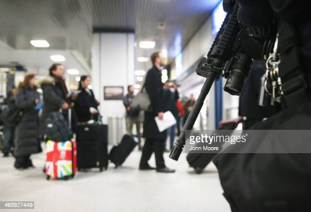 An Amtrak policeman standsguard with assault rifle at Manhattan's Penn Station as people line up to board a train on January 30 2014 in New York City...