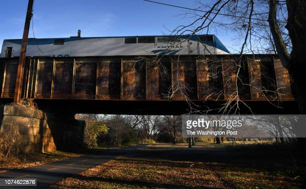 An Amtrak train on the rusting Long Bridge crosses over the hiker/biker trail that runs parallel to the GW Memorial Parkway in Virginia The train has...