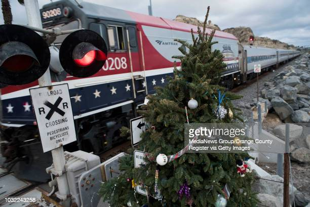 An Amtrak train passes by the Christmas tree at Calafia State Beach in San Clemente on Wednesday, Dec. 20, 2017. This year marks 10 years that Debbie...