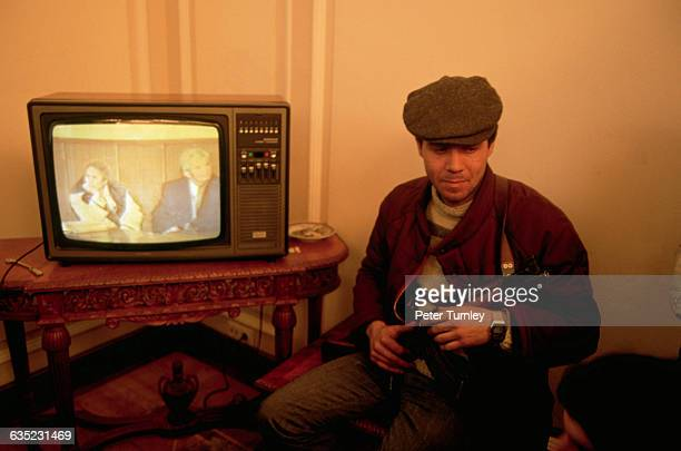 An amused armed rebel watches Nicolae Ceausescu's own office television set as it broadcasts a tape of the trial of Ceausescu and his wife Elena The...