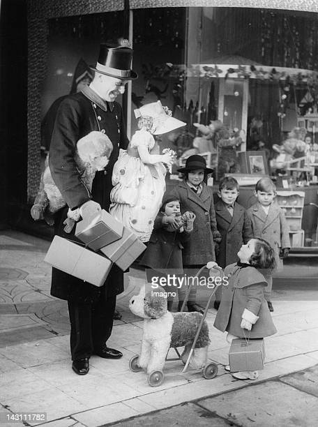 An amusing picture of the tall commissionaire chatting with a tiny shopper as she waits for a taxi London United Kingdom Photograph December 17 1936