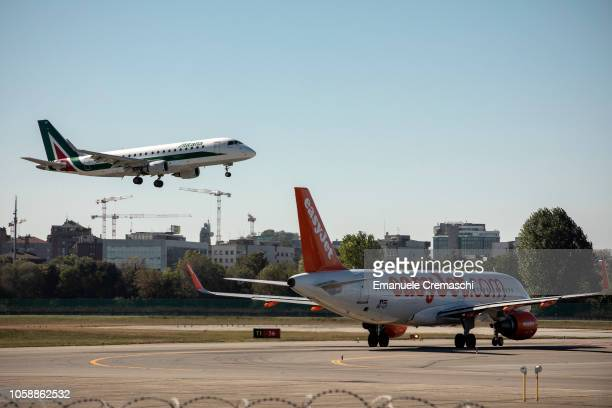 An An Embraer E175 passenger aircraft operated by Alitalia lands at Linate airport while an Airbus Airbus A320214 operated by EasyJet taxis on the...