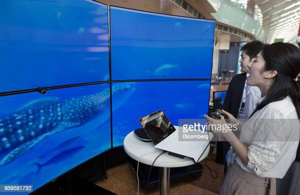 An ANA Holdings Inc employee operates a controller while taking a virtual tour of an aquarium during a demonstration at a news conference on the ANA...