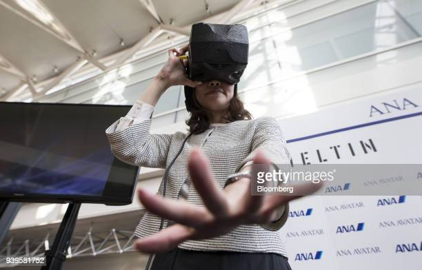 An ANA Holdings Inc employee reaches out her hand while wearing a virtualreality headset during a demonstration at a news conference on the ANA...