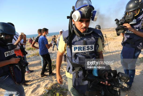 An Anadolu Agency cameraman Muntasir esSavvaf is seen after he was hit by Israeli forces' tear gas canister on his foot during the intervention of...