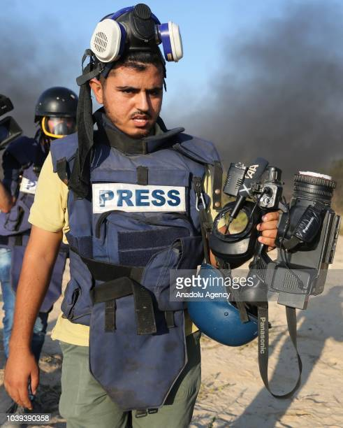 An Anadolu Agency cameraman Muntasir esSavvaf shows his damaged camera after he was hit by Israeli forces' tear gas canister on his foot during the...