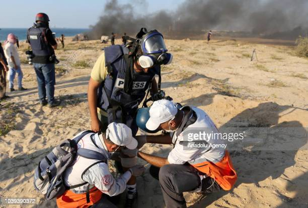 An Anadolu Agency cameraman Muntasir esSavvaf with his damaged camera receives treatment after he was hit by Israeli forces' tear gas canister on his...