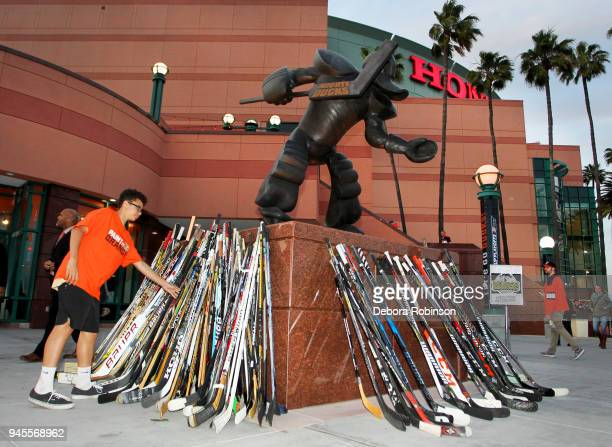 An Anaheim Ducks fan places a stick against the Wild Wing sculpture outside Honda Center to honor the victims of the Humboldt tragedy prior to Game...