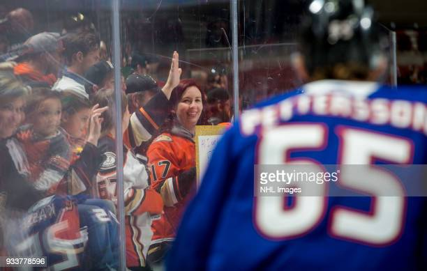 An Anaheim Ducks fan watches as Marcus Pettersson of the Anaheim Ducks skates during warmup before the game against the New Jersey Devils at Honda...
