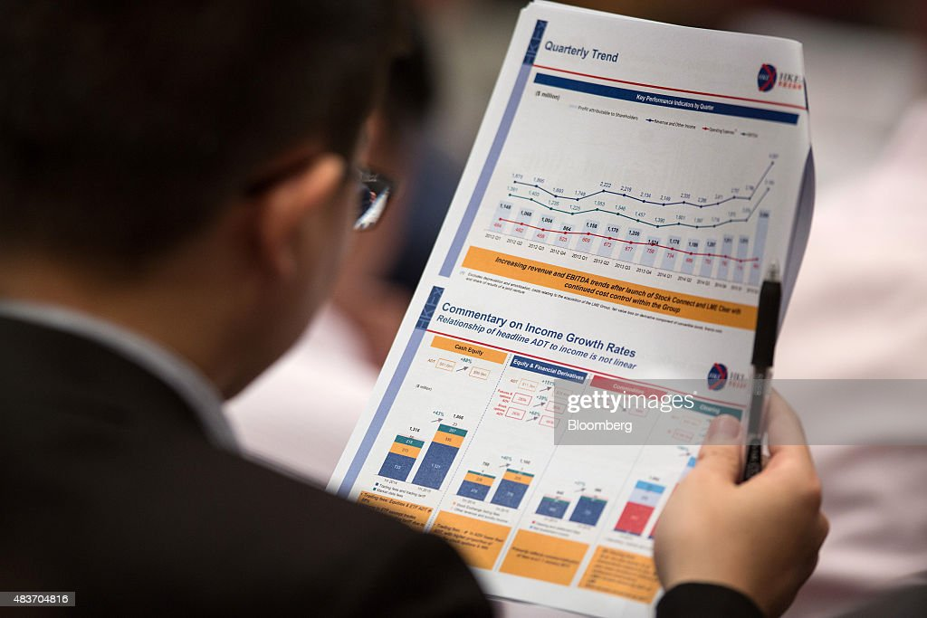 An analyst reads a brochure from the Hong Kong Exchanges and Clearing Ltd. (HKEx), during the company's earnings news conference in Hong Kong, China, on Wednesday, Aug. 12 2015. Hong Kong Exchanges headed for its steepest slide in two weeks after the bourse operator's profit missed estimates. Photographer: Jerome Favre/Bloomberg via Getty Images