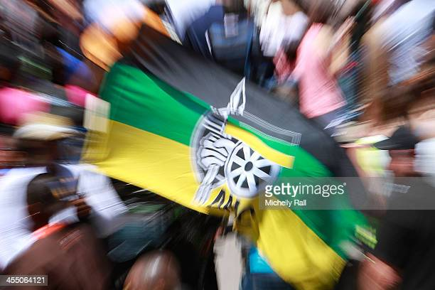 An ANC flag is seen as people watch the official memorial service for late South African President Nelson Mandela on big screens at the Grand Parade...