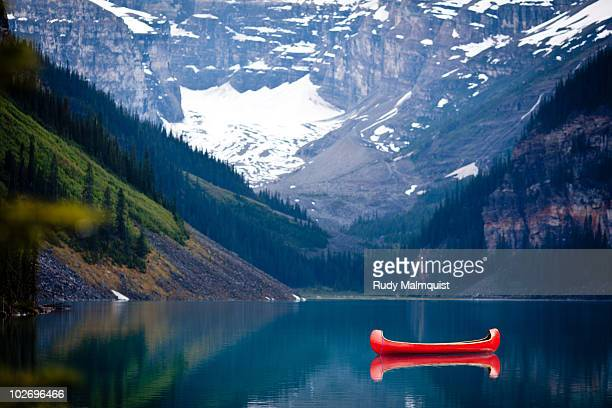 an anchored red canoe - lake louise lake stock photos and pictures