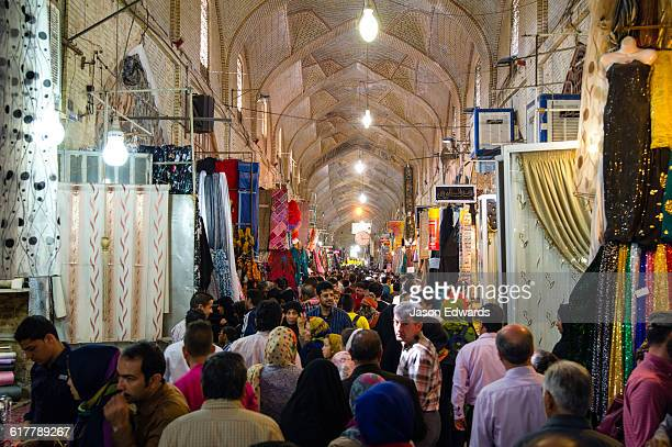An ancient bazaar crowded with people browsing and shopping from stalls during Nowruz Iranian New Year.
