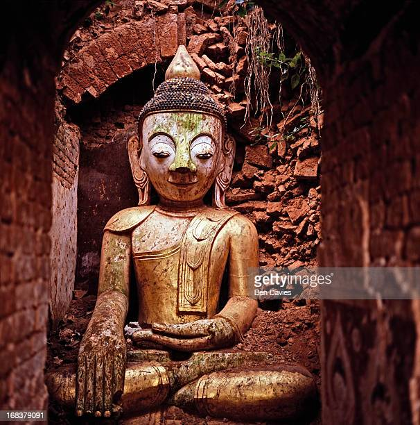 An ancient Buddha statue sits inside one of the many crumbling stupas in the ruins of Indein situated on the western bank of Inle Lake Inle is one of...