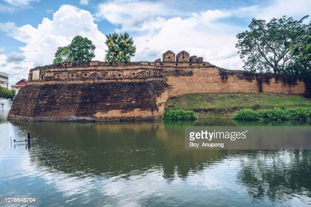 an ancient city wall in the downtown of chiang mai province of thailand. - moat stock pictures, royalty-free photos & images