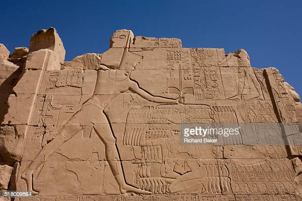 An ancient Egyptian relief showing Pharaoh Thutmosis III slaying Canaanite captives from the Battle of Megiddo 15th Century BC seen at Karnak Luxor...