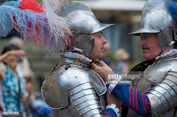An ancient knight needs a hand to hook the helmet. From the procession of historic Florentine soccer.