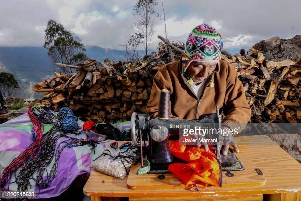An andean man makes protective masks on June 12 2020 in Ayata Bolivia Andean women sew and embroider face masks with traditional Andean themes which...
