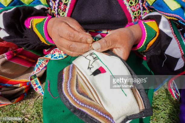 An andean woman embroiders a protective mask on June 12 2020 in Ayata Bolivia Andean women sew and embroider face masks with traditional Andean...