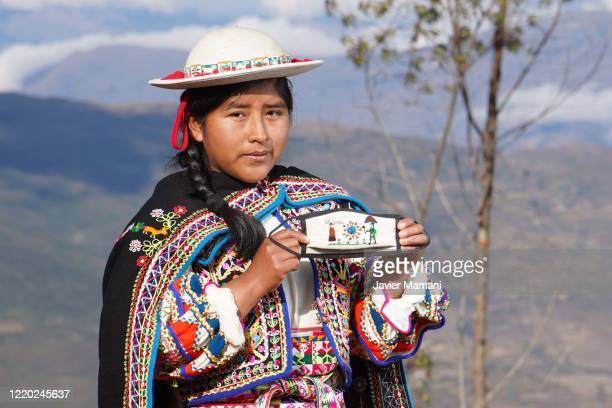 An andean woman poses with a finished protective mask with traditional theme on June 12 2020 in Ayata Bolivia Andean women sew and embroider face...