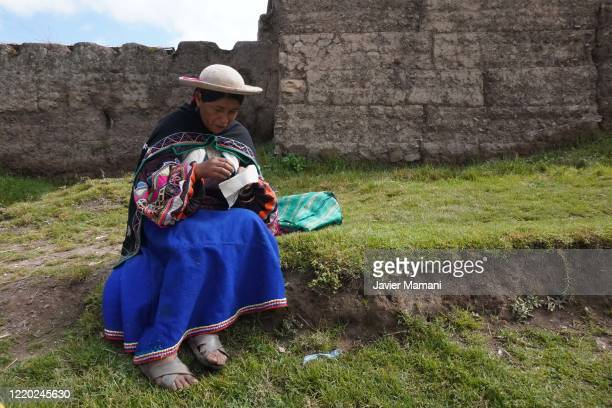 An andean woman sews a protective mask with a traditional theme on June 12 2020 in Ayata Bolivia Andean women sew and embroider face masks with...