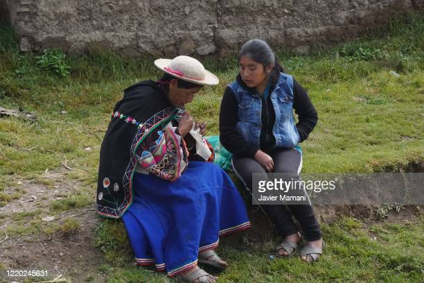 An andean woman teaches her daughter how to embroider the protective masks on June 12 2020 in Ayata Bolivia Andean women sew and embroider face masks...