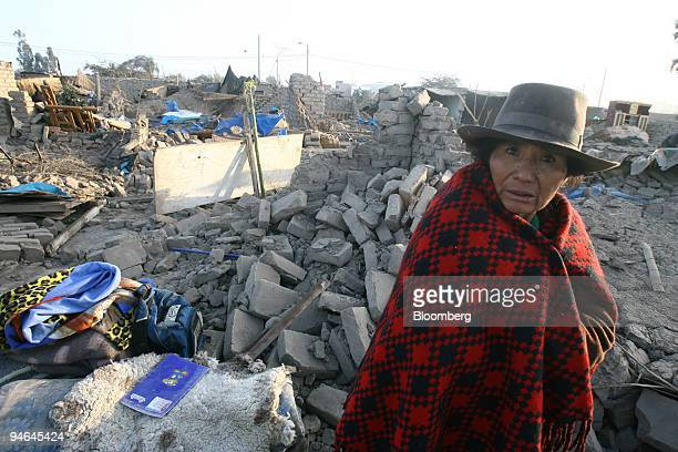 An Andean woman walks by the remains of her house in the town of Pisco Peru on Thursday Aug 16 2007 The death toll from Peru's worst earthquake in...