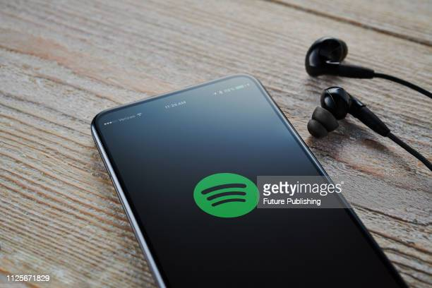 An Android smartphone with the Spotify Music logo visible on screen alongside a pair of earphones taken on February 7 2019