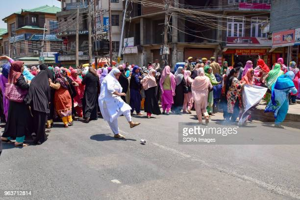 LAL CHOWK SRINAGAR JAMMU KASHMIR INDIA An Anganwadi Worker ' type of rural mother and child care centre workers'' kicks a a tear gas canister thrown...