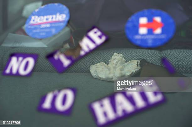An angel is displayed in the rear window of a car with campaign stickers of Bernie Sanders and Hillary Clinton and another stating No Time To Hate...