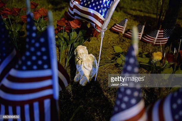 An angel statue sits in a makeshift memorial near the scene of a shooting at a Armed Forces Career Center/National Guard recruitment office on July...