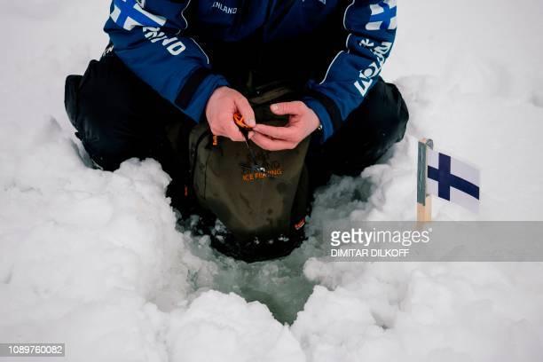 An angler from Finland team takes his position during the XVI World Ice Fishing Championship at the Shiroka Polyana dam near Batak on January 26 2019...