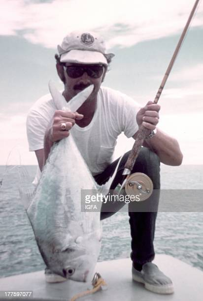 An angler kneels on the bow of a boat holding his fly rod and an African pompano caught in the United States circa 1980