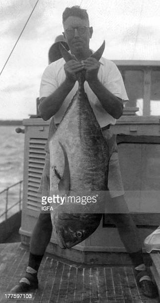 An angler stands on a fishing boat holding a large African pompano caught in the Sulu Sea near Zamboanga Philippines circa 1940