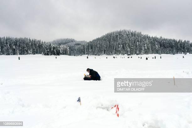 An angler takes part in the XVI World Ice Fishing Championship in Shiroka Polyana dam near Batak on January 26 2019 They battled with snow drifts and...