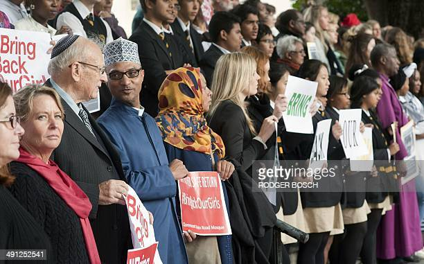 An Anglican priest and an Imam hold signs along with other people taking part in an interfaith silent vigil at the St. George's Cathedral, to call...