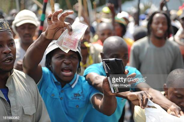 An Anglo platinum mine worker waves money in the air during a strike over disputes about their wages on September 13 2012 in Rustenburg South Africa...