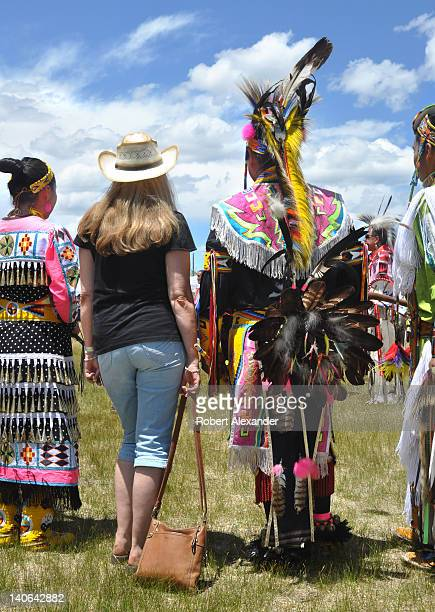 An anglo visitor to the annual Taos Pow Wow poses for a photo with a group of NativeAmerican dancers The annual summer event in Taos Pueblo New...