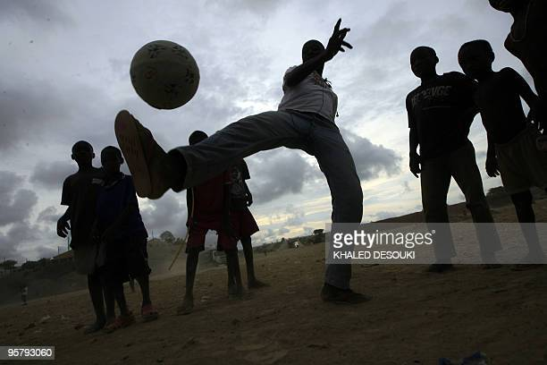 An Angolan boy kicks up the ball outside the Stadium of petroleum Academic in Lobito village about 20 km out of Benguela on January 14 2010 during...