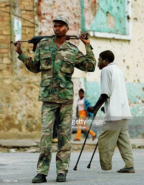 An Angolan soldier known as 'Bernardo' walks through the destroyed town of Cuito Angola March 5 2000 as a man who lost his leg to a landmine walks on...